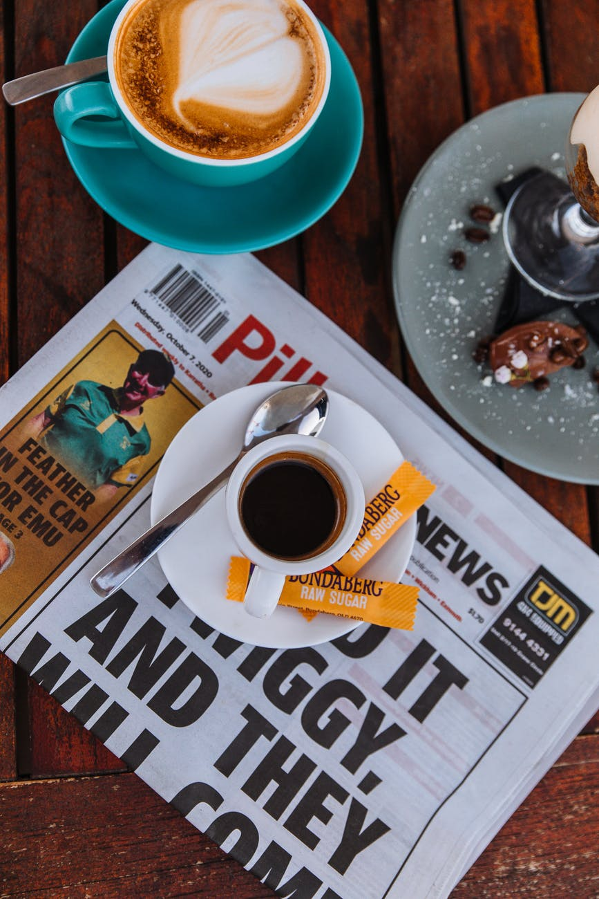 Image of a mug, coffee beans, a cup of coffee, sugar packets, and a newspaper.
